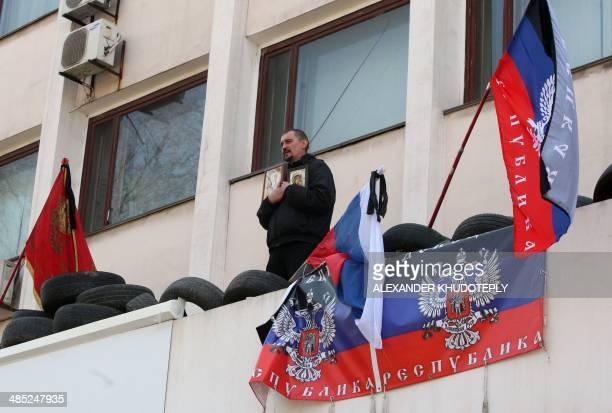 A proRussia activist holds icons as he prays on a balcony of the city government building seized by the separatists in the southeast city of Mariupol...