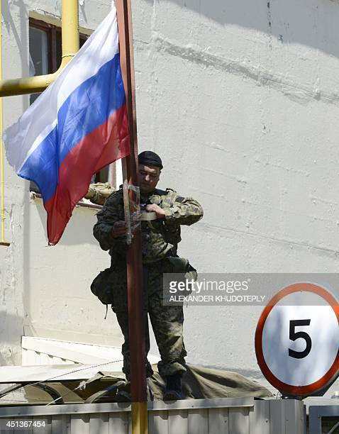 A proRussia militant ties a Russian national flag on a fence at the Ukrainian National Guard unit seized by the separatists in the eastern Ukrainian...