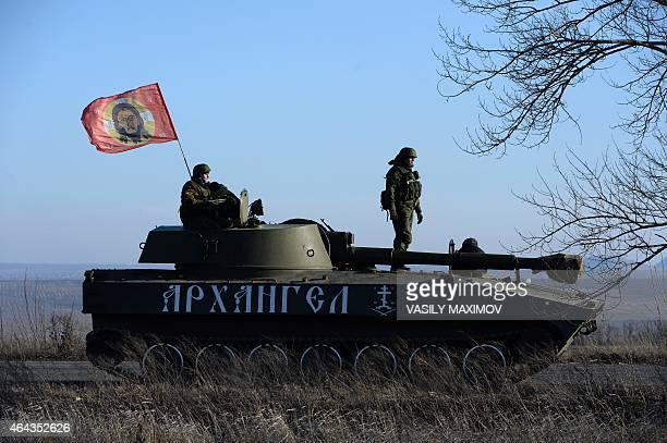 ProRussia militants sit next to a flag with the face of Jesus Christ as a convoy of 2S1 Gvozdikas takes a break as they move from the frontline near...