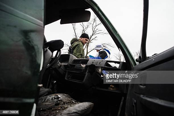A proRussia rebel and an International observer of the Organization for Security and Cooperation in Europe stand next a destoyed car after shelling...
