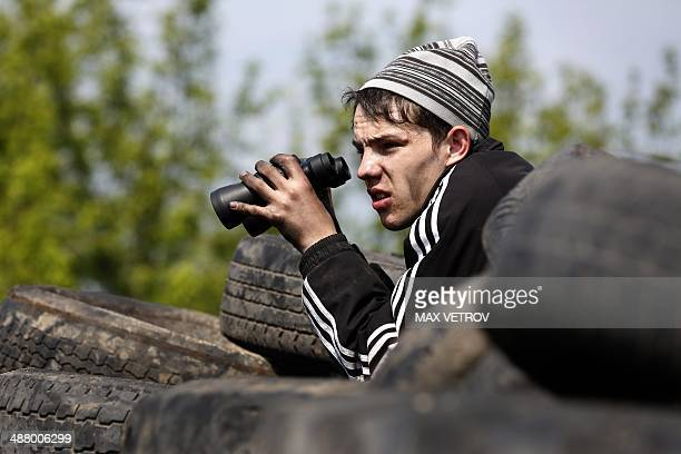 Pro-Russian activist holds binoculars at a checkpoint manned by pro-Russian separatists near the southern Ukrainian city of Slavyansk on May 3, 2014....