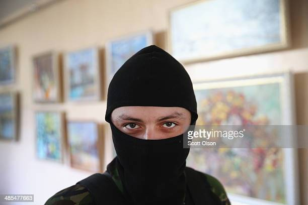 Pro-Russian activist stands guard inside the Donetsk city government building on April 18, 2014 in Donetsk, Ukraine. Nearby, activists have also...