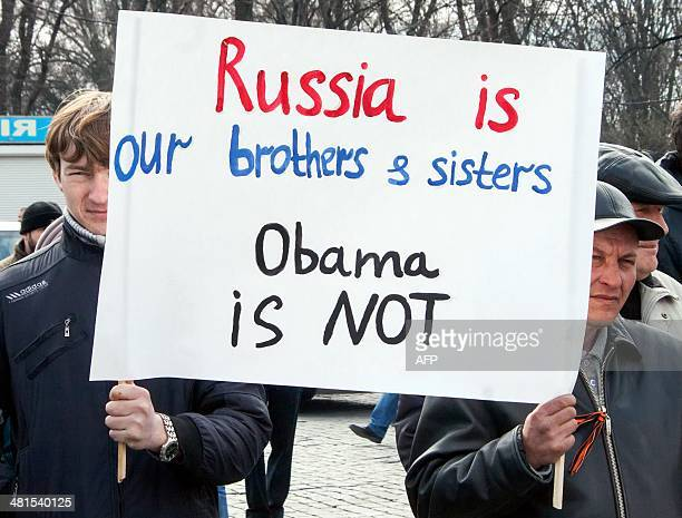 ProRussian activists hold a placard as they take part in a rally in front of the Lenin monument in Kharkiv on March 30 2014 US Secretary of State...