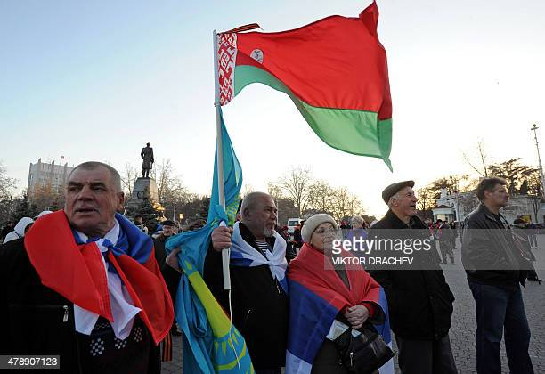 ProRussian activists hold the flags of Russia Kazakhstan and Belarus during a gathering in Sevastopol on March 15 2014 Crimea's referendum on March...