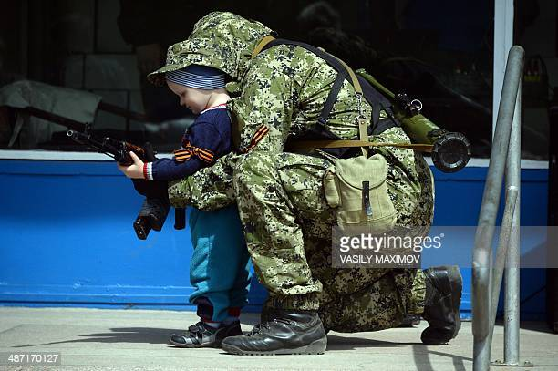 A proRussian armed man in military fatigues poses for a photograph with a child as he stands guard outside a regional administration building seized...