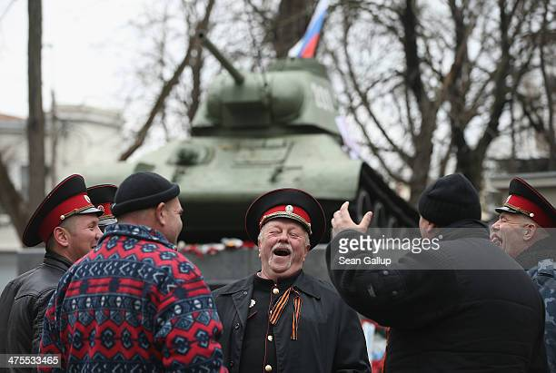 Pro-Russian Cossacks share a laugh next to a war monument at a gathering of pro-Russian supporters outside the Crimean parliament building on...