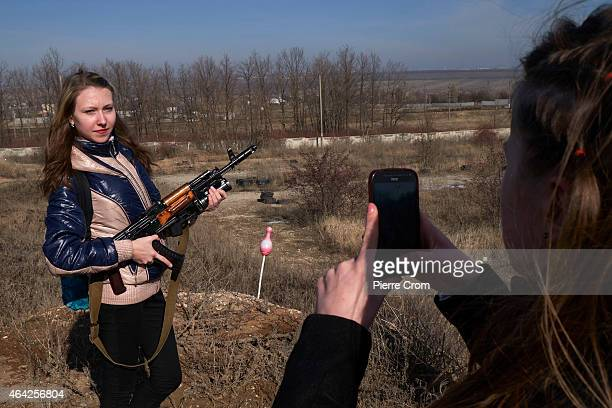 ProRussian Donetsk residents pose with weaponry as people celebrate the Russian festival 'Defender of the Fatherland' day on February 23 2015 in...