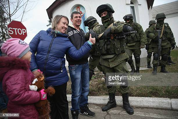 A proRussian family pose for snapshots with soldiers who had taken up positions around a Ukrainian military base in Crimea on March 2 2014 in...