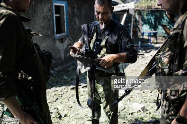 proRussian gunman holds a piece of shrapnel from a rocket after shelling in downtown Donetsk on August 22 2014 Ukraine accused Moscow of invading...