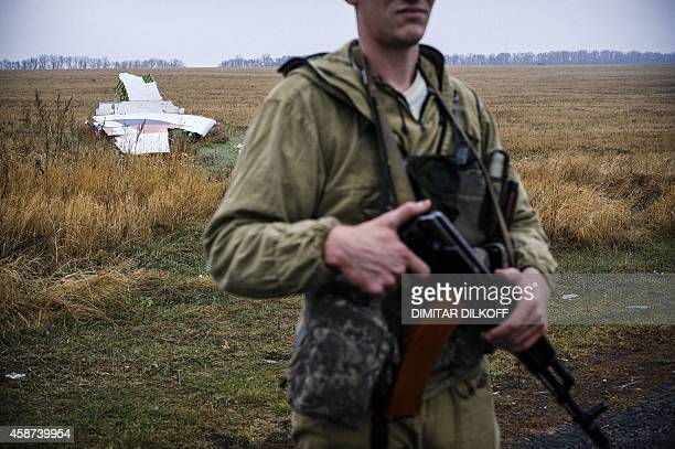 A proRussian gunman stands guard on November 10 2014 next to parts of the Malaysia Airlines Flight MH17 at the crash site near the village of Hrabove...
