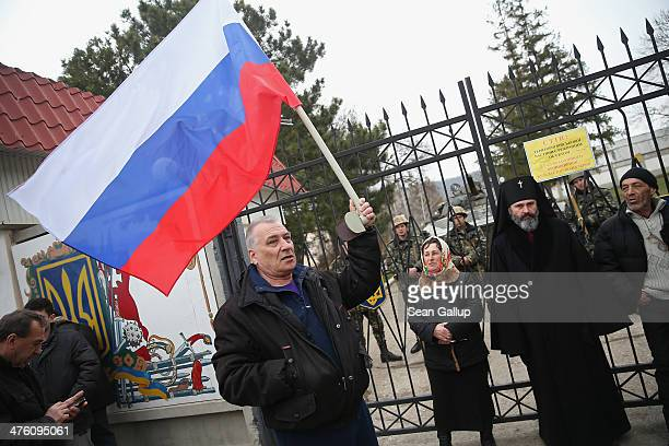 A proRussian man waves a Russian flag next to an Orthodox clergyman standing to bar access to the gate outside a Ukrainian military base that was...