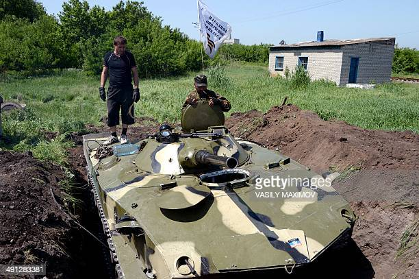 ProRussian militants conceal an armoured personnel carrier as they reinforce their checkpoint in the village of Semyonovka near the eastern Ukrainian...