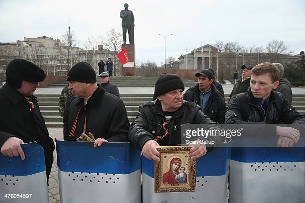 Pro-Russian militants station themselves behind a row of shields near a local government building and a statue of Lenin on March 2, 2014 in...