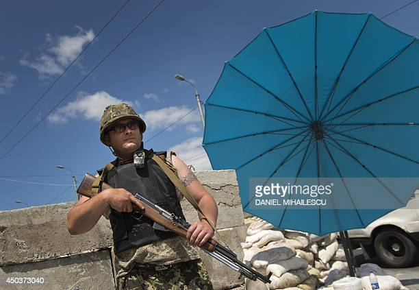 A proRussian militia man from the Russian Orthodox Army stands at a check point near the airport in Donetsk city on June 10 2014 Ukraine's new...