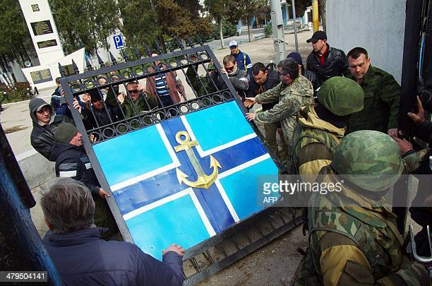 Pro-Russian protesters remove the gate of Ukrainian navy headquaters as Russian troops stand guard in Crimean city of Sevastopol on March 19, 2014....