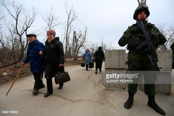 A proRussian rebel guards a checkpoint in Stanytsia Luhanska Lugansk region on March 7 as an elderly couple passes into Ukrainecontrolled territory...