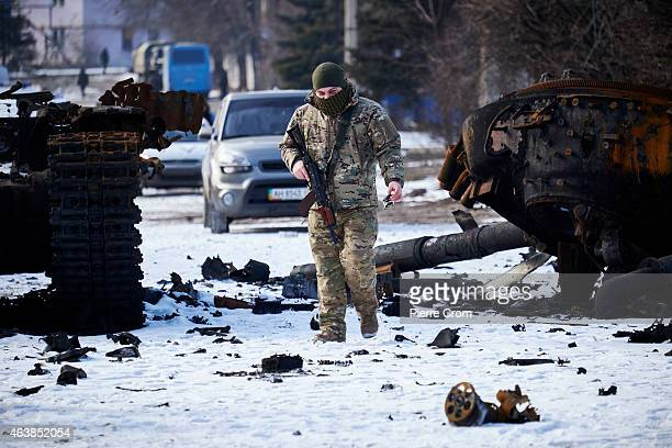 ProRussian rebel looks at the remains of a Ukrainian tank as people from the ministry for civil defense and emergencies of the 'Donetsk People's...