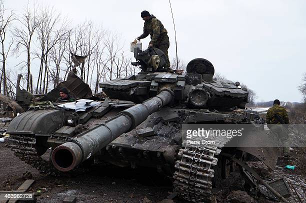 A proRussian rebel stands atop a Ukrainian tank on the outskirt of the town on February 20 2015 in Debltseve Ukraine The strategic railway town of...