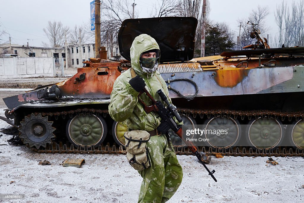 A pro-Russian rebel walks by a destroyed Ukrainian military vehicle on February 7, 2015 in Uglegorsk, Ukraine. According to Pro-Russian rebels, control of Uglegorsk, on the frontline near Debaltseve, was regained two days ago, after eight days of fierce fighting.