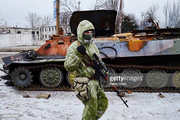 A proRussian rebel walks by a destroyed Ukrainian military vehicle on February 7 2015 in Uglegorsk Ukraine According to ProRussian rebels control of...