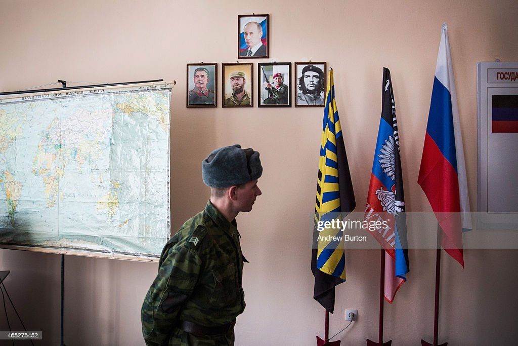A pro-Russian rebel walks past a portrait of Russian President Vladmir Putin and pro-communtist leaders at Battalion Kalmius headquarters on March 5, 2015 in Donetsk, Ukraine. Over 6,000 people have been killed since the conflict between Ukraine and pro-Russian rebels started last April.