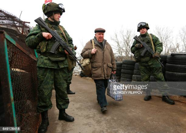 ProRussian rebels guard a checkpoint in Stanytsia Luhanska Lugansk region on March 7 as an elderly man carrying bags passes into Ukrainecontrolled...