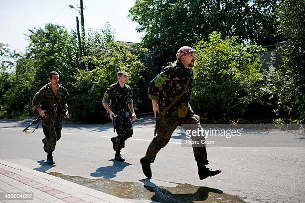 ProRussian rebels rush to a fire in a residential area of Donetsk named Voroshyloskyi after it was hit by artillery shelling on August 14 2014 in...