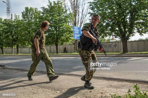 ProRussian separatist fighters take positions outside the Donetsk airport the scene of an hourslong battle between proRussian separatists and...
