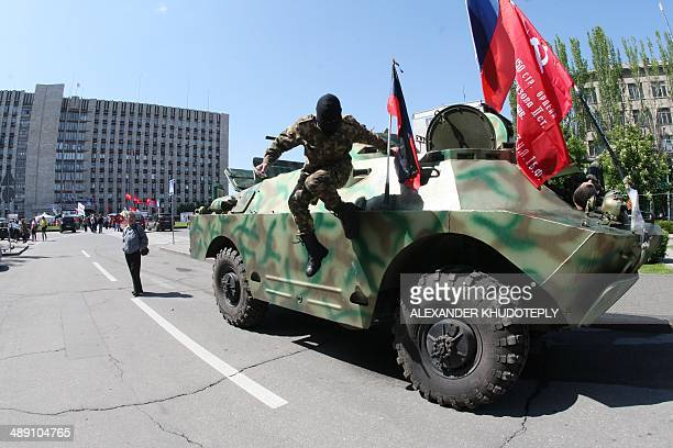 A proRussian separatist jumps off an armored vehicle parked in front of the regional state building in eastern Ukrainian city of Donetsk on May 10 n...