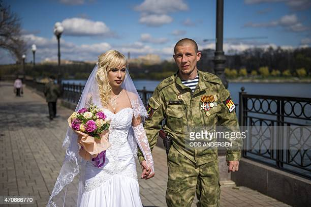 ProRussian separatist Junga and his bride walk along river Kalmius after getting married in Donetsk on April 22 2015 in the selfproclaimed Donetsk...