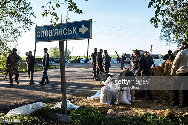 ProRussian separatist militants fill sand bags to reinforce a checkpoint on April 24 2014 in Slovyansk Ukraine ProRussian activists have been...