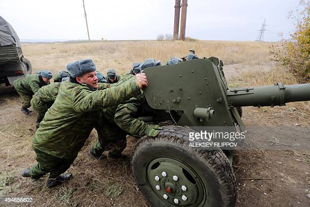 ProRussian separatists push an MT12 Rapira 100mm antitank gun into a hangar in the village of Zelene Donetsk region on October 28 2015 The antitank...
