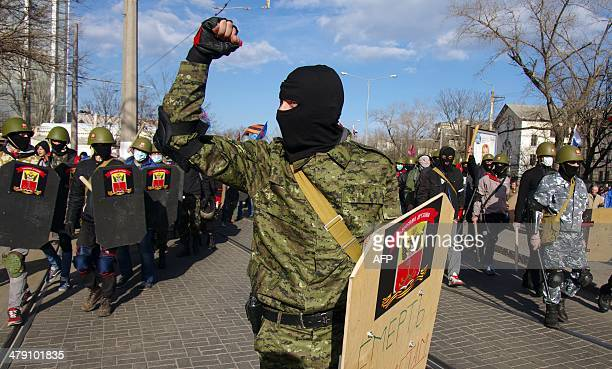 Pro-Russian supporters wearing balaclava and military helmets while holding shields march during a rally in the center of the Ukrainian city of...