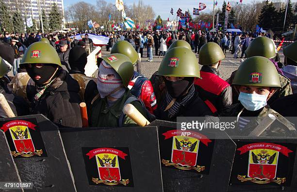 Pro-Russian supporters wearing balaclava and military helmets while holding wooden clubs and shields attend a rally in the center of the Ukrainian...