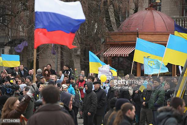 Pro-Russian sympathizers bearing a Russian flag march past pro-Ukrainian sympathizers gathered and waving Ukrainian flags on March 8, 2014 in...