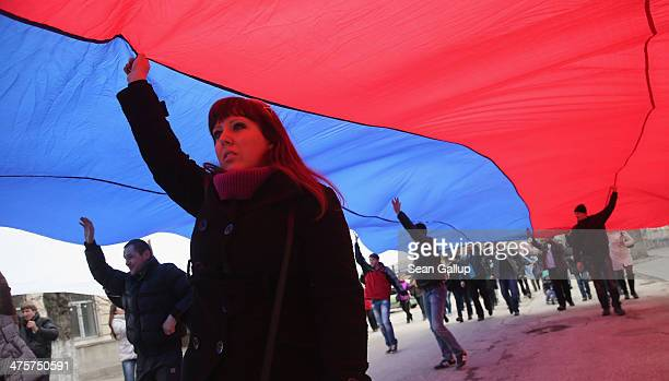 """Pro-Russian sympathizers chanting """"Russia, Russia! Simferopol, Simferopol! Sevastopol, Sevastopol! Berkut, Berkut!"""" hold up a giant Russian flag as..."""