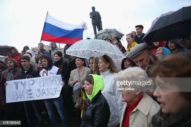 ProRussian sympathizers hold a small rally under a statue of Lenin on March 5 2014 in Simferopol Ukraine Meanwhile armed paramilitary troops...