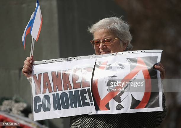 """Pro-Russian sympathizers, including an elderly woman holding a sign that reads: """"Yankee Go Home!"""", attend an anti-American rally hours after..."""