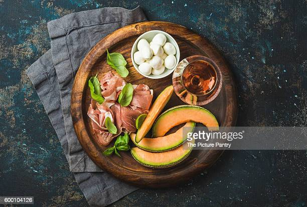 Prosciutto ham, cantaloupe melon, mozzarella cheese, fresh basil leaves and glass of rose on wooden round serving board over grunge dark plywood background