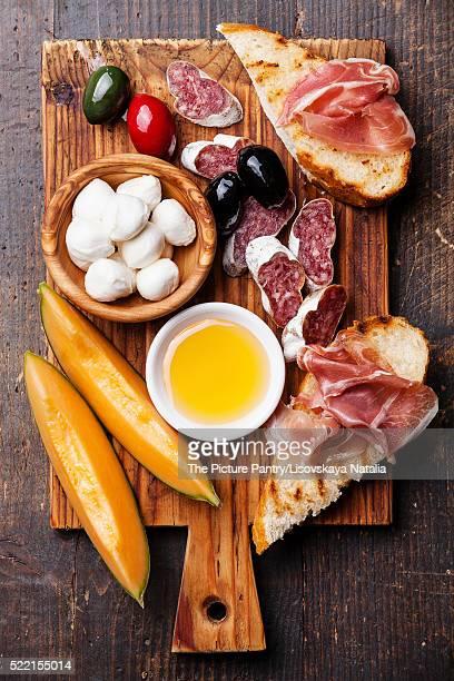 Prosciutto ham, Slices of melon cantaloupe, Mozzarella cheese an