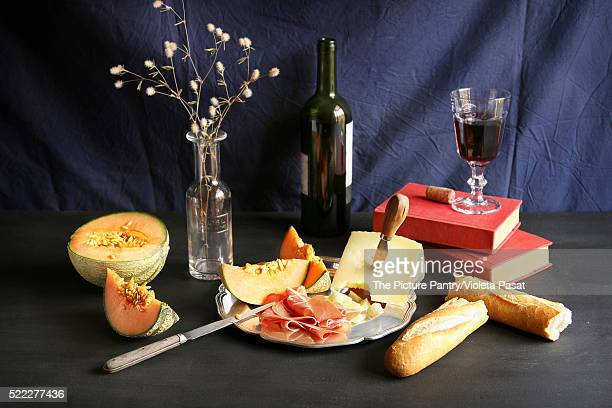 Prosciutto,cheese and melon on a plate with a bottle of wine and a jar with dried flour on backgroun