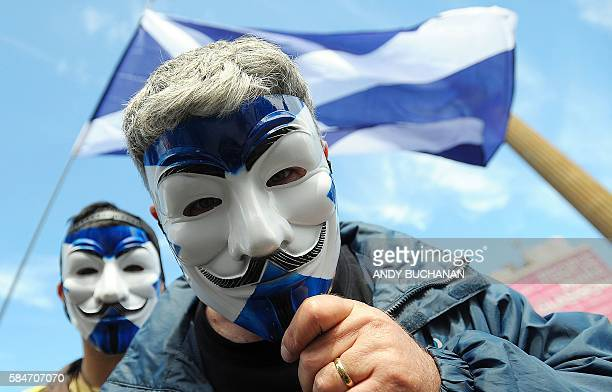 TOPSHOT ProScottish Independence supporters with Scottish Saltire flag masks pose for a picture at a rally in George Square in Glasgow Scotland on...