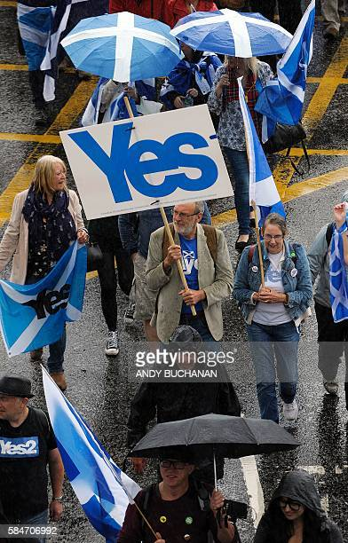 ProScottish Independence supporters with Scottish Saltire flags and a 'Yes' banner march toward George Square for a rally in Glasgow Scotland on July...