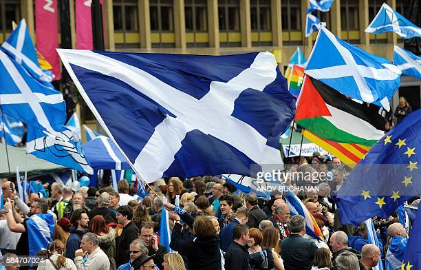 ProScottish Independence supporters with Scottish Saltire flags and EU flags among others including the Palestinian flag rally in George Square in...