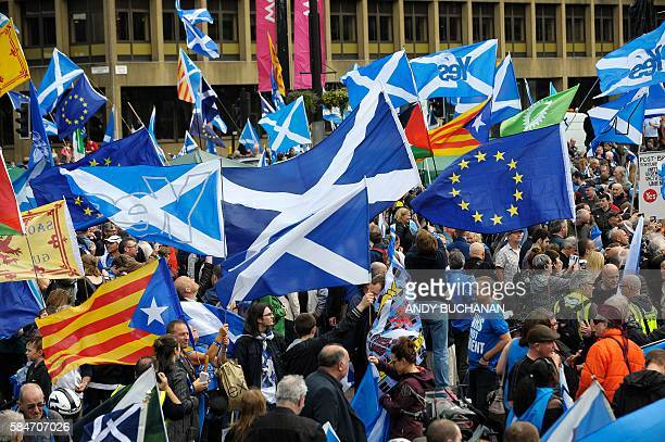 ProScottish Independence supporters with Scottish Saltire flags and EU flags among others including the Estelada the unofficial flag of Catalan...