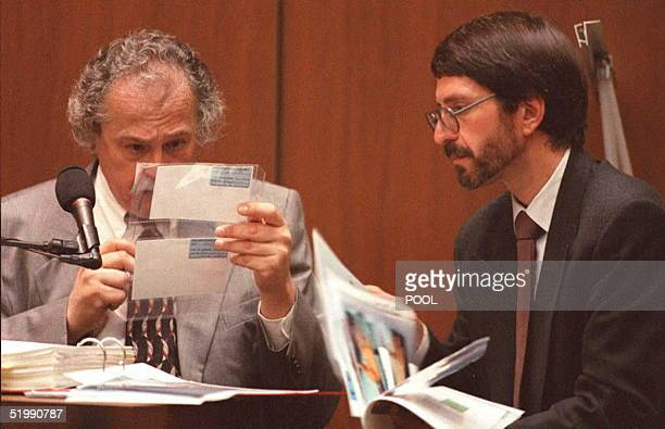 Prosecutor Brian Kelberg looks on as forensic pathologist Michael Baden examins photographs 10 August showing cuts to the hands of defendant O.J....