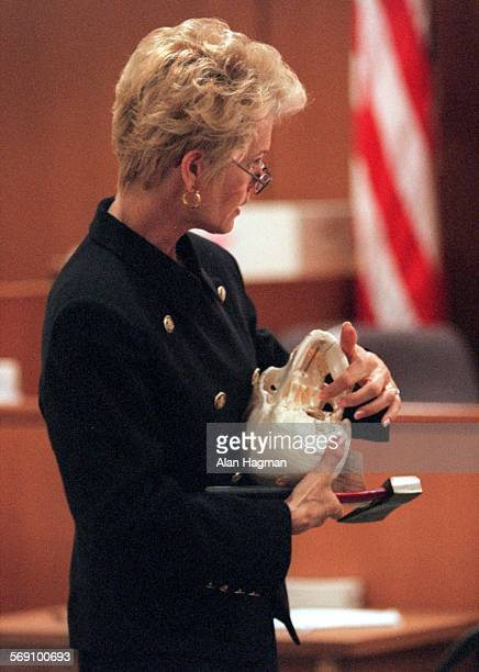 Prosecutor Lela Henke–Dobroth holds a skull and an axe as she describes to the jury wounds inflicted to the head of Sherri Dally allegedly by Diana...