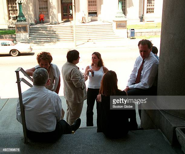 Prosecutor Rick Grundy right leaning against column and others wait outside Norfolk Superior Court as the jury deliberates in the trial of Dr Dirk...
