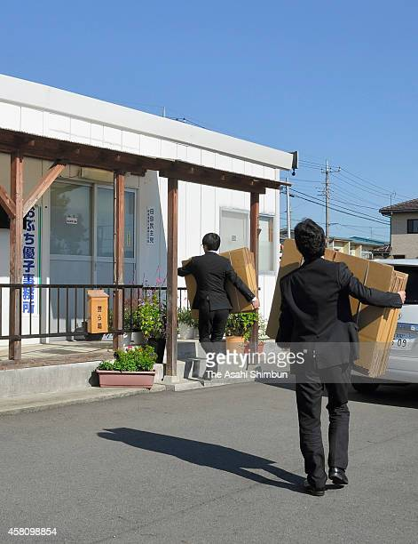 Prosecutors walk in with cardboard boxes to search former trade minister Yuko Obuchi's Takasaki electoral support office on October 30, 2014 in...