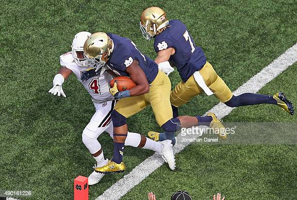 J Prosise of the Notre Dame Fighting Irish completes a 57 yard touchdown run by running over Randall Jette of the Massachusetts Minutemen at the...